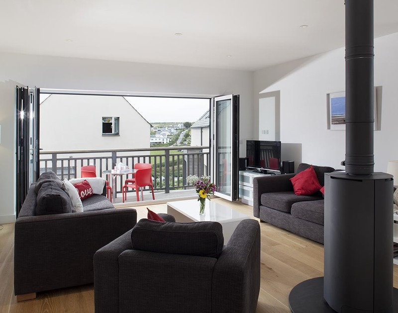 The open plan living room with glass doors out to the balcony at Carnweather, a self catering holiday house to rent in Polzeath, Cornwall.