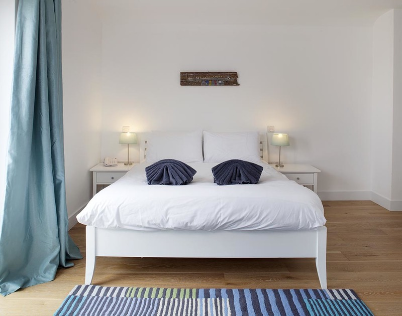 The bright, elegant king size bedroom with an en-suite in Carnweather, a self catering holiday house to rent in Polzeath, North Cornwall.