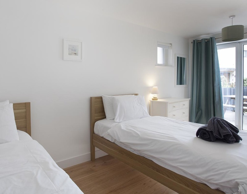 A contemporary twin bedroom with access onto the private decked terrace in Carnweather, a self catering holiday home in Polzeath, Cornwall