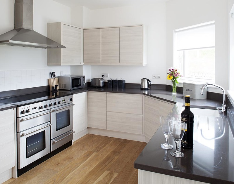 The contemporary well equipped kitchen with a range cooker in the open plan first floor at Carnweather, a self catering holiday rental in Polzeath, Cornwall.