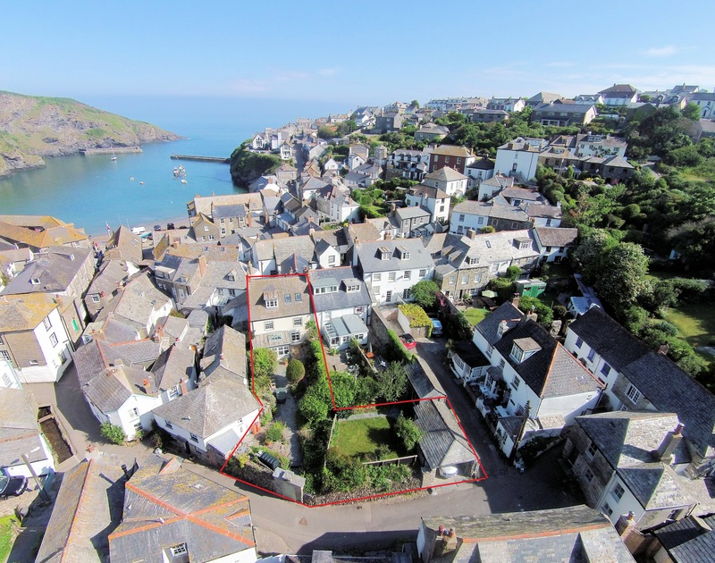 An aerial view of the harbourside location of Trevan House, a holiday house in Port Isaac, Cornwall, with red boundary line indicating the large garden.