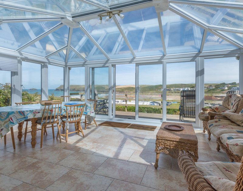 A large bright conservatory over-looking the garden and beach at Polzeath, with access out on to a sun deck.