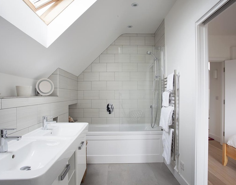 The stylish ensuite bathroom at Kellan a holiday home in Polzeath, Cornwall has his and hers basins and an over bath shower.