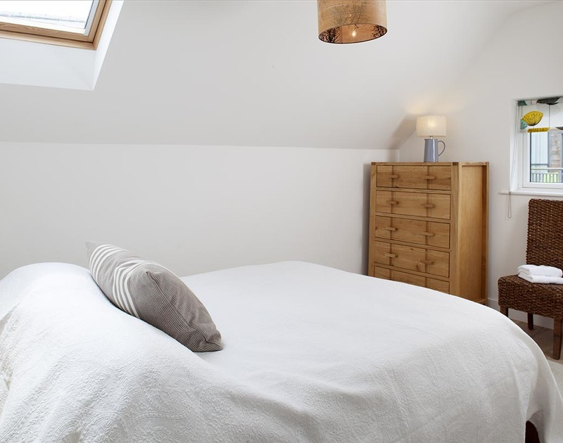 The bright double bedroom with adjoining ensuite shower room at Kellan, a self catering holiday home in Polzeath, north Cornwall.