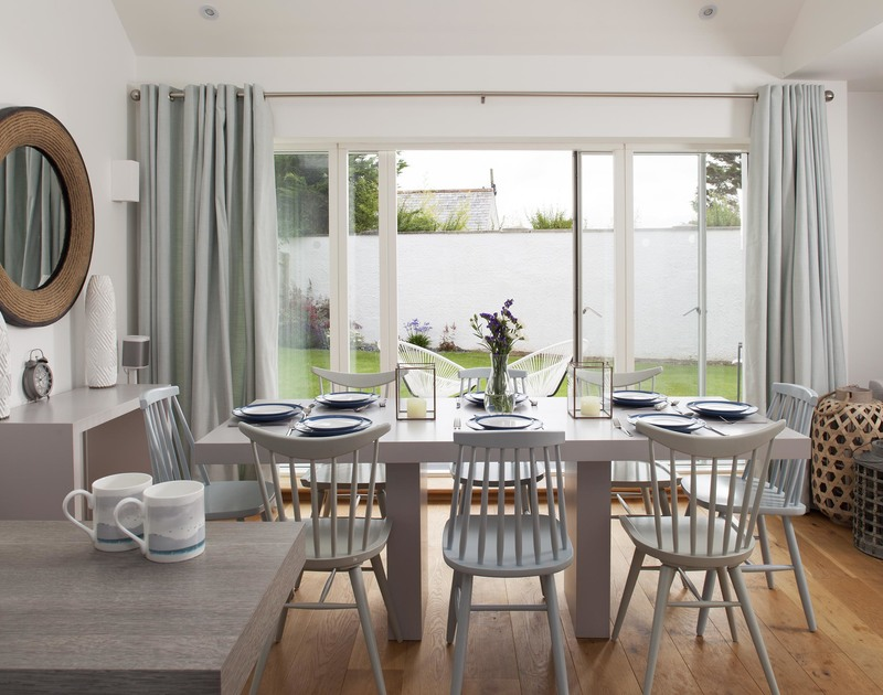 The stylish light-filled dining room with glass doors to the garden at 5, The Sands, a luxury holiday rental in Polzeath, North Cornwall.