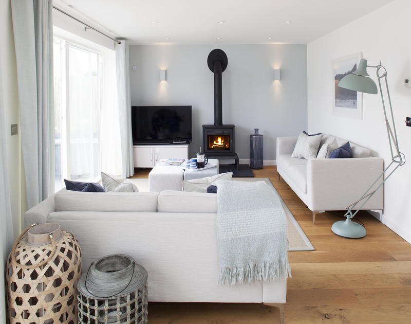 The contemporary lounge with modern log burner and flat screen TV at 5, The Sands, a luxury self catering holiday rental in Polzeath, Cornwall.