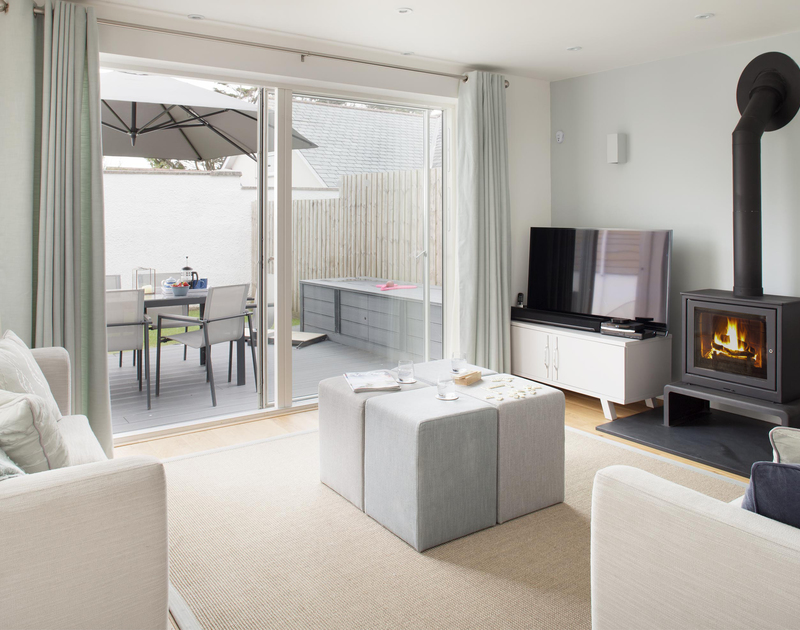 The modern open plan living room at 5 The Sands in Polzeath opens onto a lovely lawned garden with decking.