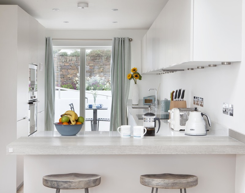 Socialise with dinner guests over the breakfast bar in the sleek white kitchen at 5 The Sands, a holiday home in Polzeath