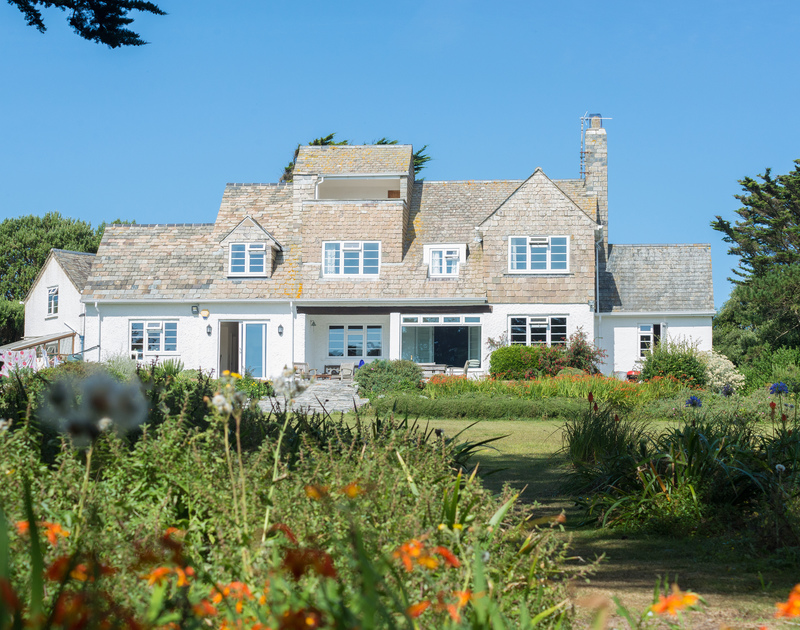 The exterior view of Doom Bar House, a stunning holiday house to rent at Daymer Bay, Cornwall, with its large lawned garden.