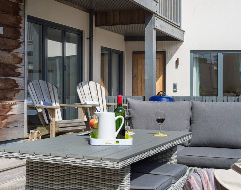 Room to sit and enjoy meals or drinks outside on the decking at Rainer Rocks, just up hill from the beach and sea at Polzeath in North Cornwall.