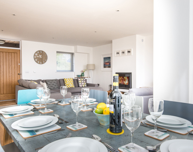 Welcoming dining table by the sofa and contemporary woodburner on the spacious open plan first floor at Rainer Rocks in Polzeath, North Cornwall.