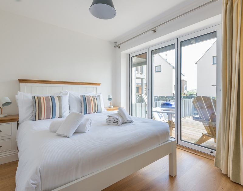 The downstairs king size double bedroom with bi-fold doors onto the balcony at Rainer Rocks, a self catering holiday house in Polzeath, North Cornwall.