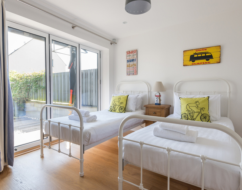 Pretty twin bedroom with access outside to sunny decked area from bi-fold doors at Rainer Rocks, a self catering luxury holiday house to rent in Polzeath, Cornwall.