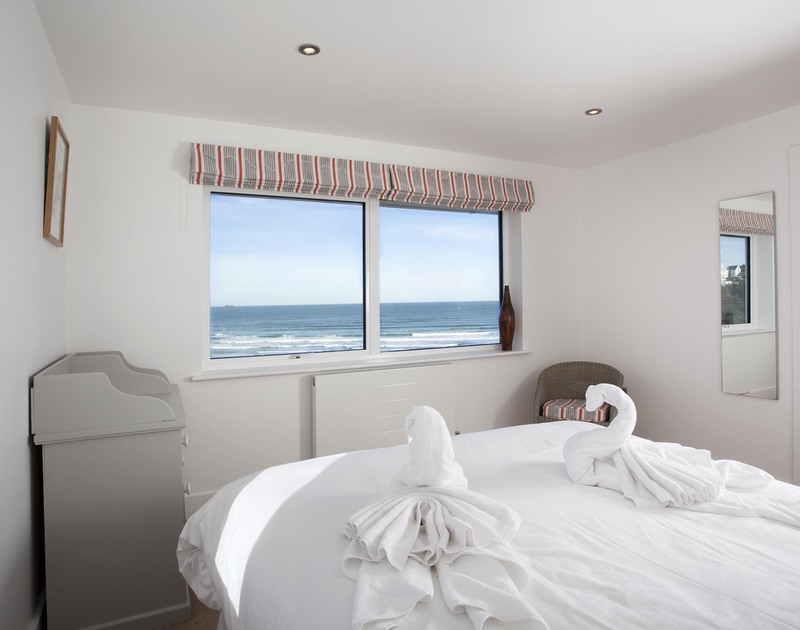 Bedroom two at The Whitehouse in Polzeath offers stunning sea views and an adjacent large ensuite bathroom with corner bath.