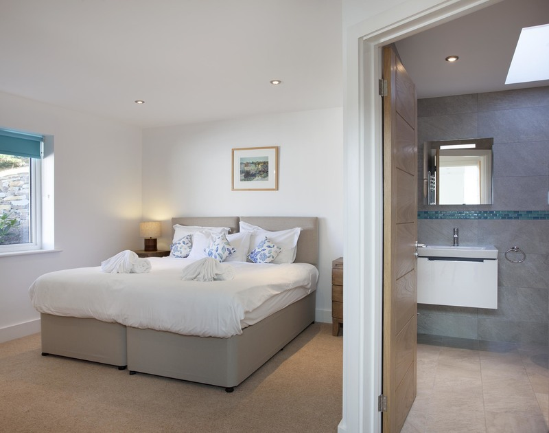 The twin bedroom at The Whitehouse in Polzeath on the North Cornwall coast, has an ensuite shower room and garden view.