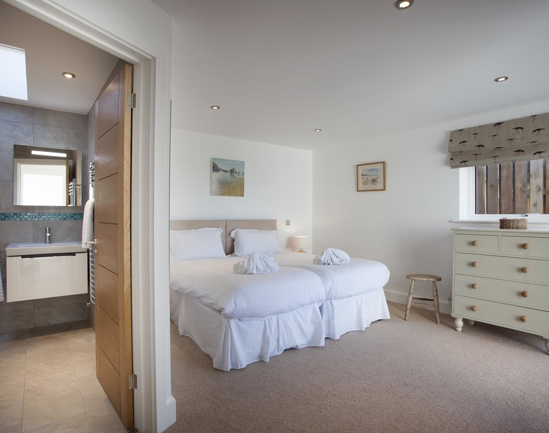 The second twin bedroom at The Whitehouse at New Polzeath, has an ensuite shower room and a balcony with sea views towards Stepper Point.