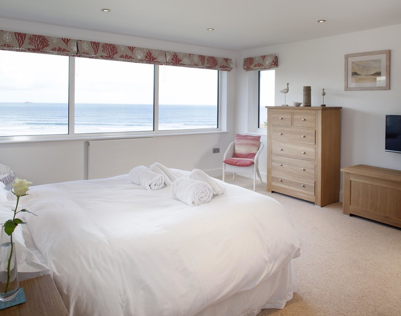 The large master ensuite bedroom at The Whitehouse in Polzeath, on the North Cornwall coast has triple aspect windows with uninterrupted sea views.