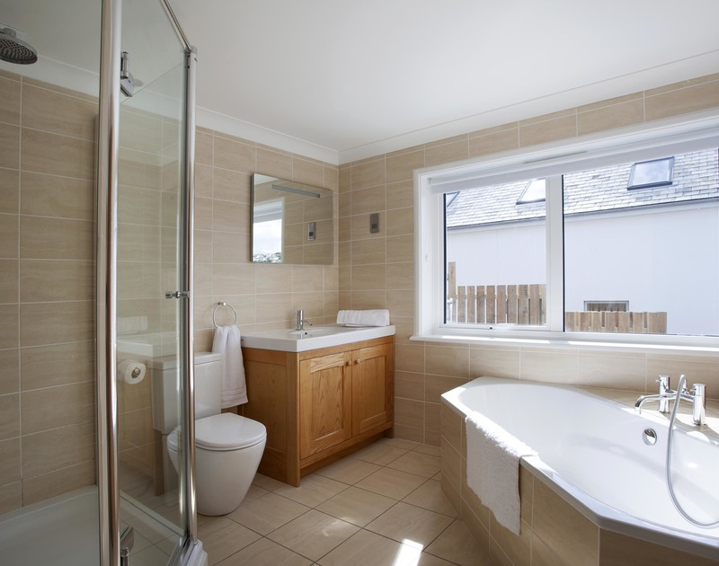 The ensuite bathroom means you can indulge in a long soak in the corner bath at The Whitehouse - a luxurious holiday house in Polzeath on the North Cornwall coast.