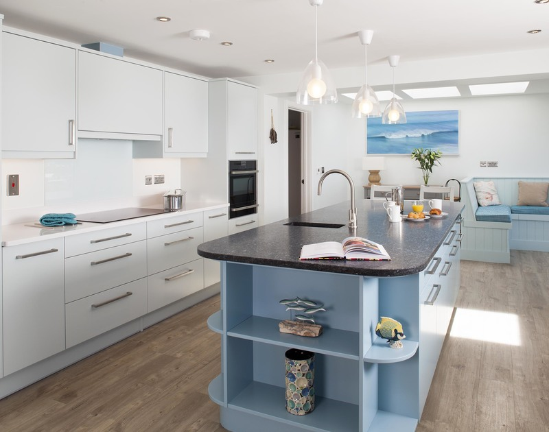 The sleek kitchen at The Whitehouse in Polzeath has an island unit, wonderful sea views, as well as an adjacent pantry and breakfast area.