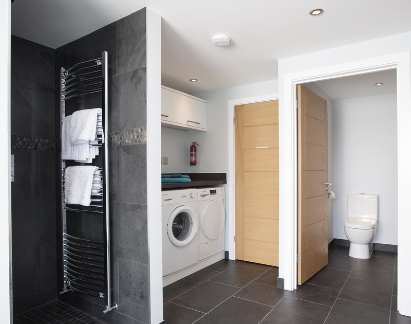 The spacious utility room at The Whitehouse, Polzeath also has a beach shower with rainfall shower head, WC and additional store room.