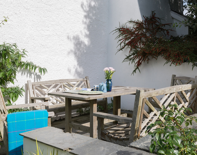 To the side of St Enodoc Cottage in Daymer Bay, Cornwall and facing the garden, is a sunny patio area with table and chairs.