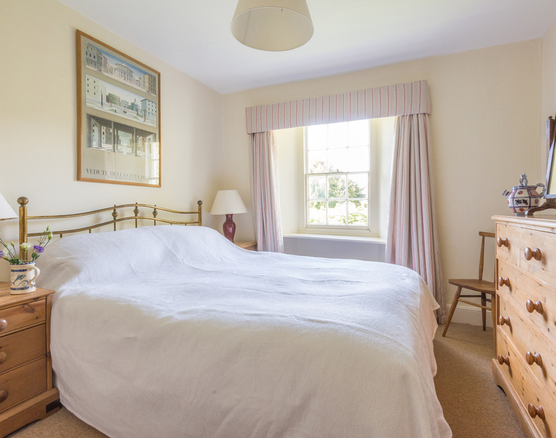 A king size bedroom with brass bed, in St Enodoc Cottage, a self catering holiday cottage to rent in Daymer Bay, Cornwall.