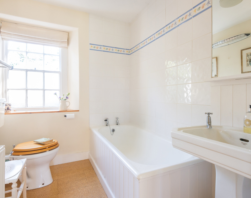 The spacious white ensuite master bathroom in St Enodoc Cottage, a self catering holiday house to rent in Daymer Bay, north Cornwall.