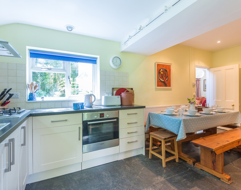 The light-filled kitchen in St Enodoc Cottage, a coastal self catering holiday cottage with original slate floors, to rent in Daymer Bay, North Cornwall.