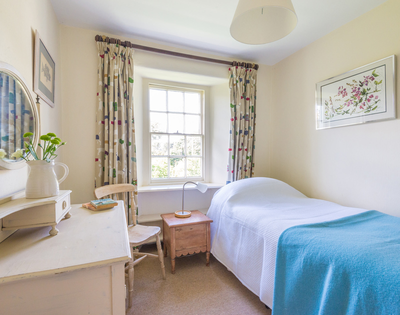The single bedroom at St Enodoc Cottage in Daymer Bay, Cornwall is light and airy with garden views.