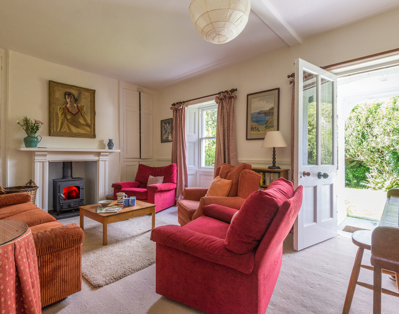 The elegant sitting room with original features and a woodburner at St Enodoc Cottage, a relaxing seaside holiday house in a peaceful position at Daymer Bay, Cornwall.
