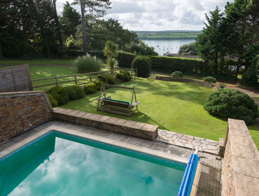 The swimming pool, large gardens and the views of the estuary from superbly positioned Speedwell, a perfect self catering Cornish holiday house to rent in Rock on the Camel Estuary in Cornwall.