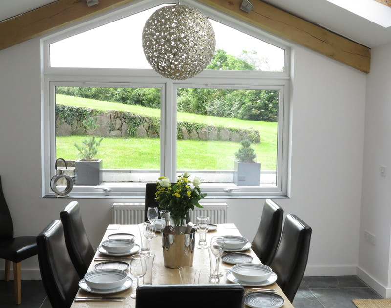 The open plan dining room at The Terrace in Port Isaac, Cornwall with views of the garden and terrace overlooking Port Isaac harbour