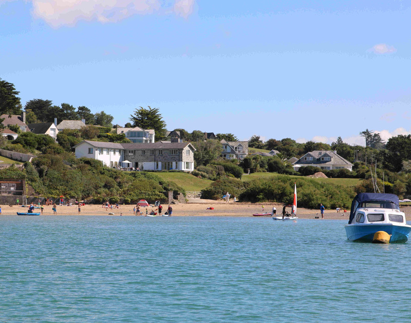 The view from the water of the beach at Porthilly with the direct access to Harbour Lights and its large lawned garden, a large luxury holiday house in Rock, Cornwall.