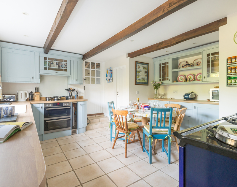 The traditional kitchen and breakfast dining area with aga and electric oven in Peppercorn Cottage, a traditional self catering holiday cottage in Rock, Cornwall