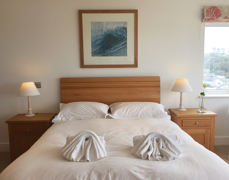 Pared back luxury in the master bedroom at The Whitehouse, Polzeath so as not to detract from the panoramic coastal sea views.