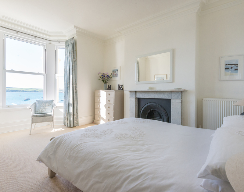 Original fireplace and bay window with stunning sea views in the master bedroom at 2, The Terrace, a self catering, holiday property overlooking the Camel Estuary in Rock.