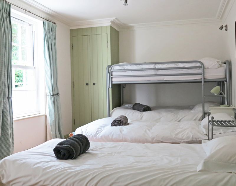 The spacious children's room at Old Brea Coach House that sleeps 4 and has an ensuite shower room set near Daymer Bay.