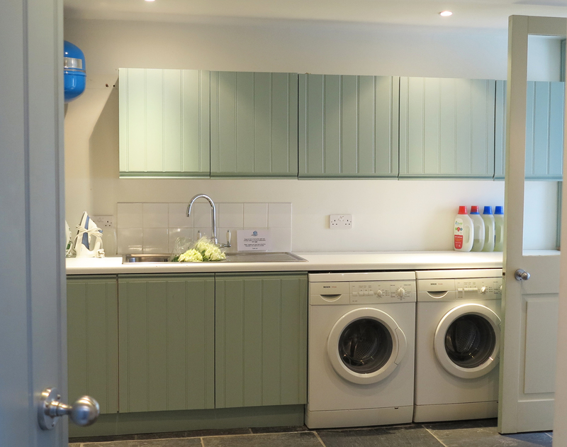 The spacious utility room at luxury self catering Old Brea Coach House, Daymer Bay, Cornwall has a door to the garden.