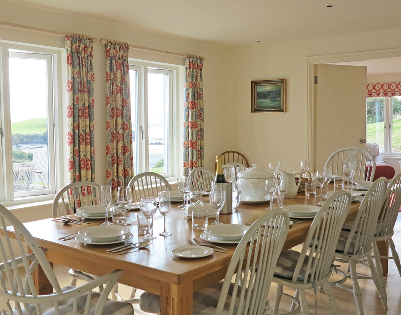 The sunny and light formal dining room of Harbour Lights, a holiday house in Rock, Cornwall, with stunning views of Porthilly Cove and the Camel estuary