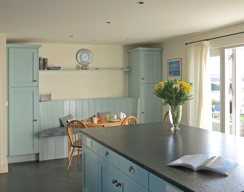 The kitchen of Harbour Lights, a holiday house in Rock, Cornwall, with its large central island, patio doors leading to the terrace and river views.