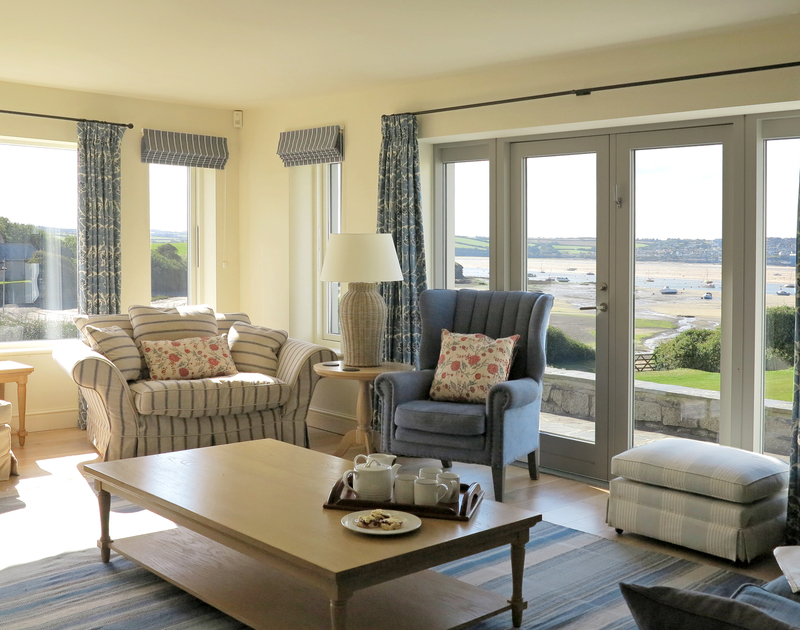 The sunny, comfortable sitting room at Harbour Lights, a luxury self-catering holiday house in Rock, Cornwall, with its lovely sea views.