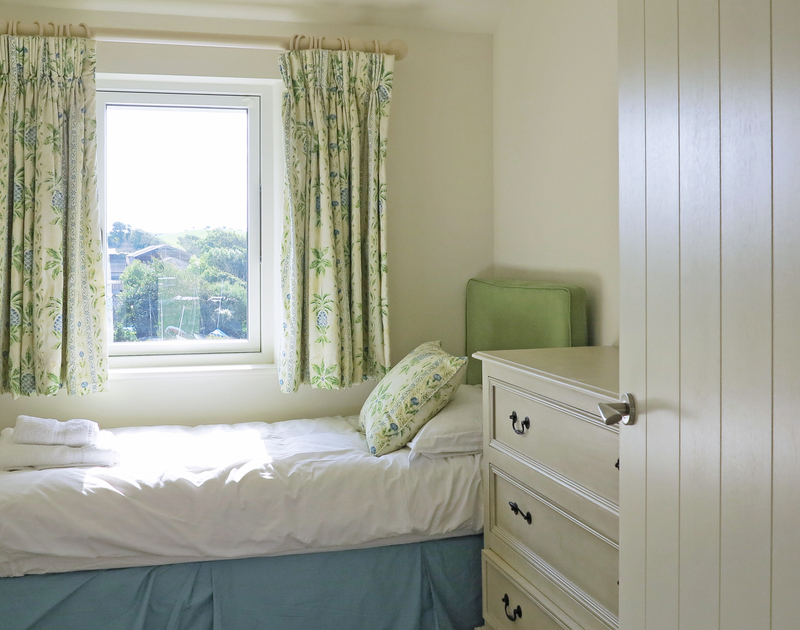 The sunny single bedroom on the first floor at Harbour Lights in Rock overlooks the boat park at Porthilly cove.