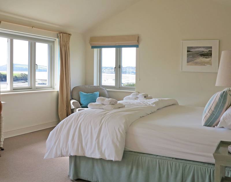 The master bedroom suite of Harbour Lights  - a holiday rental in Rock, Cornwall, has dual aspect windows to make the most of the Camel Estuary views.