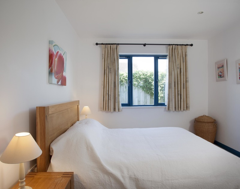 The second double bedroom at Belmont, a holiday rental in Rock, Cornwall, has an ensuite bathroom with over bath shower.