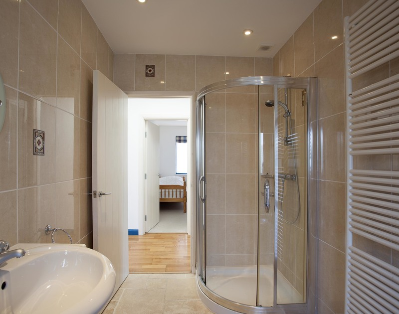 The family bathroom at Belmont in Rock, North Cornwall offers both a bathtub and a separate shower for convenience.