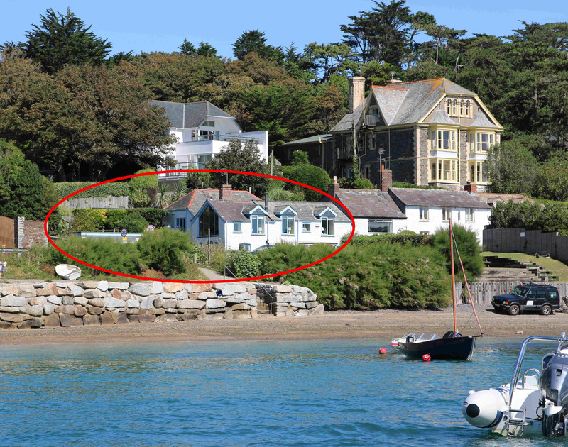 The pretty exterior and front garden at The Cottage, as seen from a boat on the water, a dog friendly holiday rental on the Camel Estuary in Rock, North Cornwall.