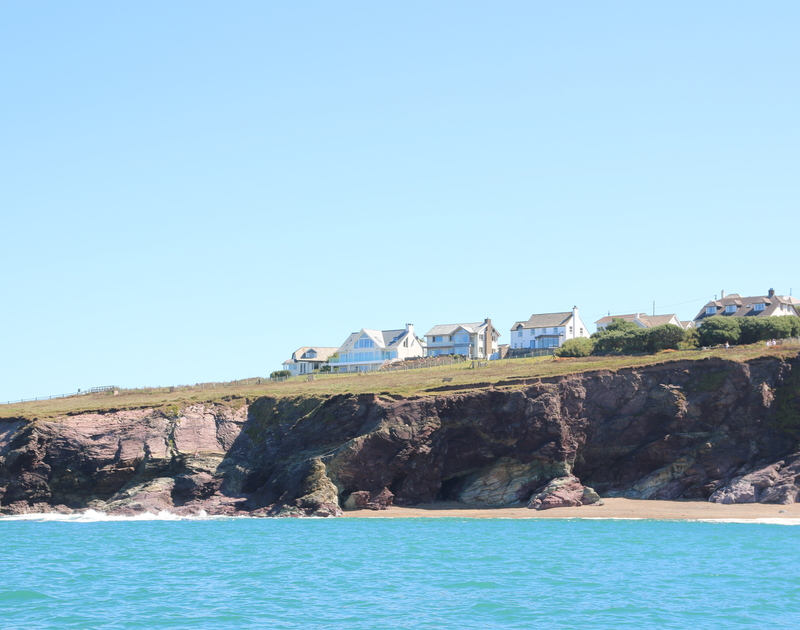 The view from a boat at sea of the front line cliff top house Treviles, a self catering holiday rental at Polzeath, North Cornwall.