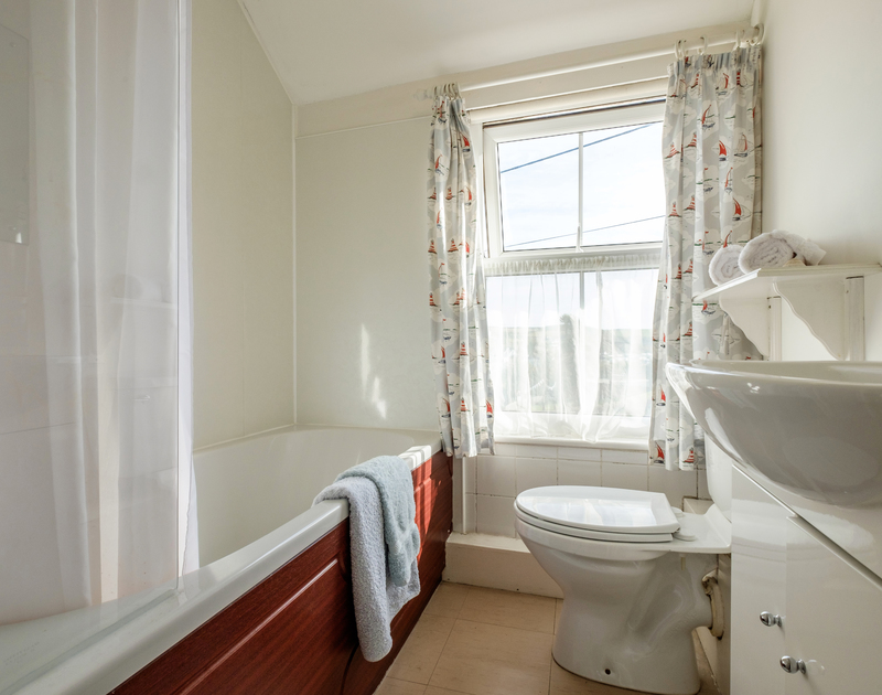 The sunny front facing family bathroom with overhead shower at Coppingers Cottage, close to Polzeath beach in Cornwall