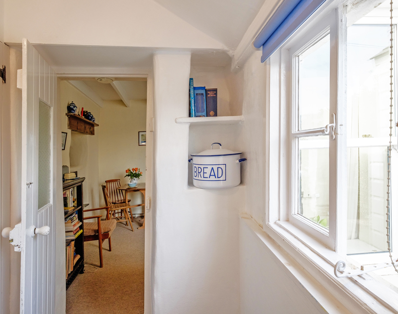 The light galley style kitchen at Coppingers Cottage is decorated in a traditional coastal whitewash