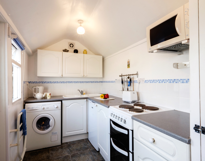 The light filled galley style kitchen at Coppingers Cottage in Polzeath adjoins the living room and has a door leading out to the front courtyard